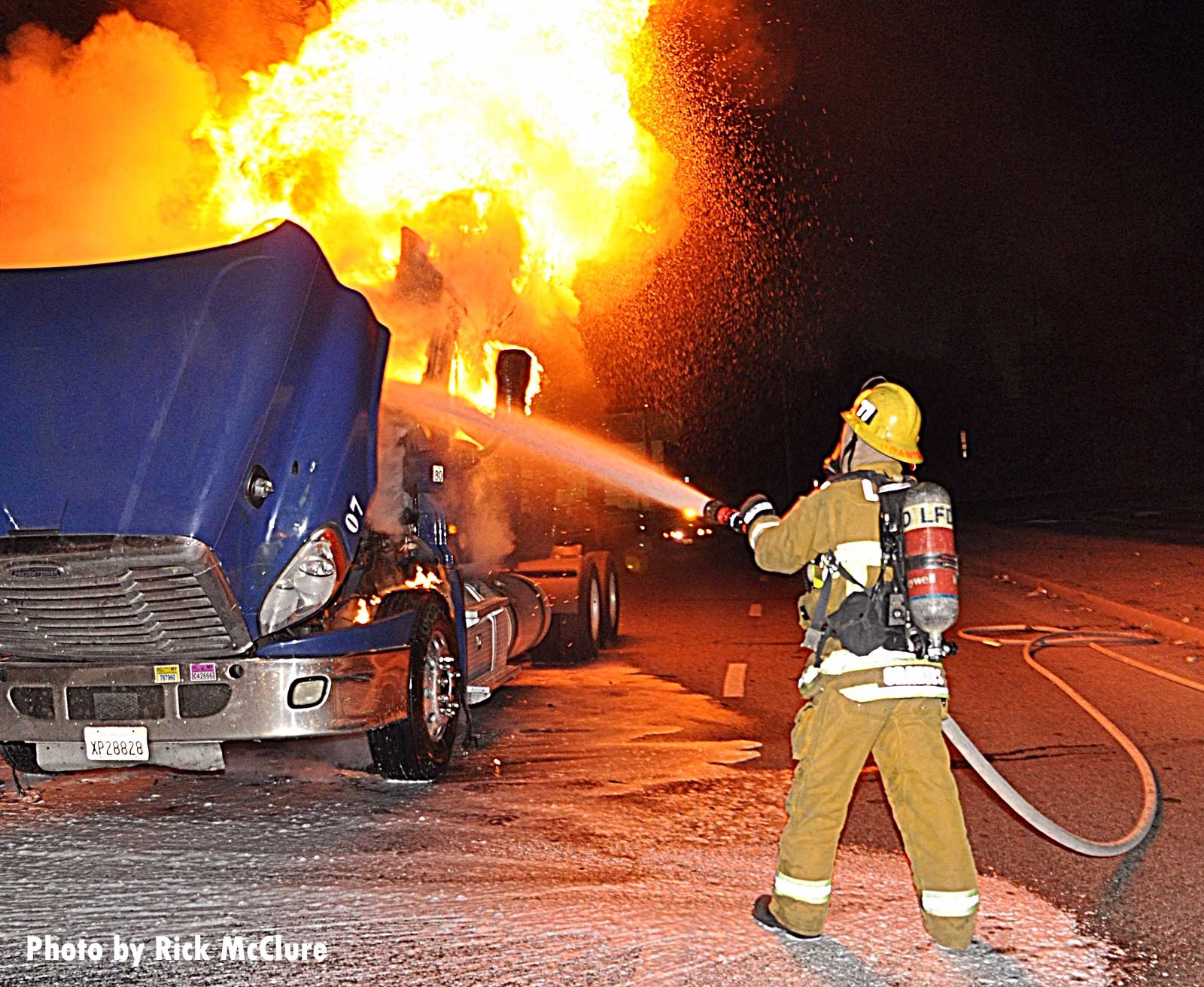 A City of Los Angeles firefighter puts water on a burning tractor trailer