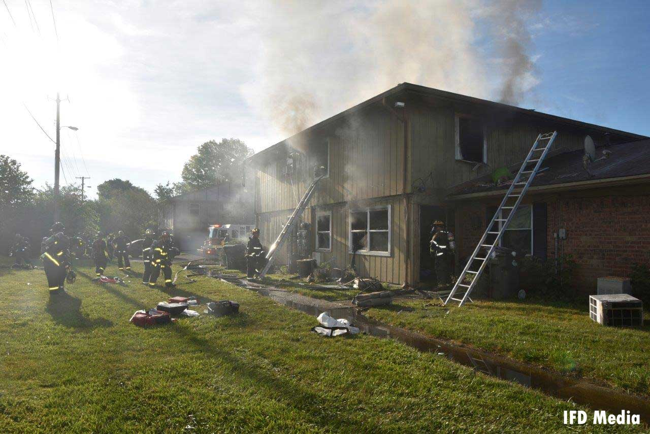 Firefighters and ladders at the scene of the fire with smoke condition