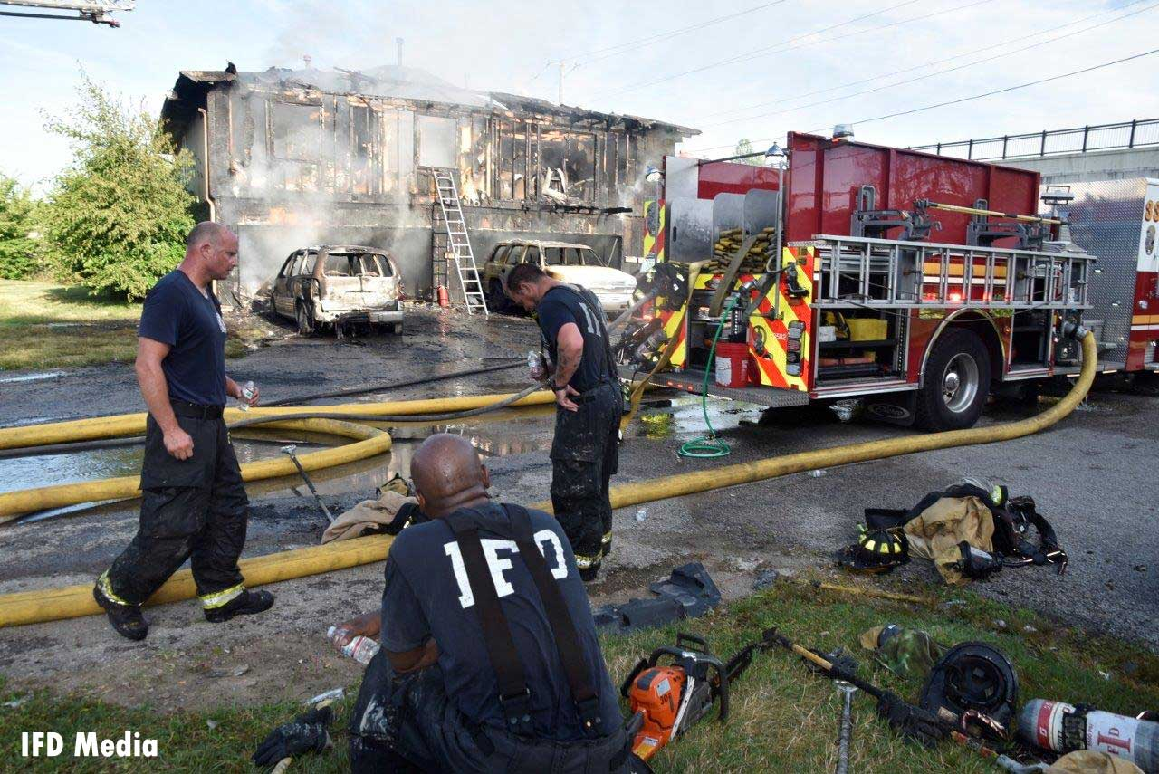 Firefighters rehab with a fire truck at the scene of the fire