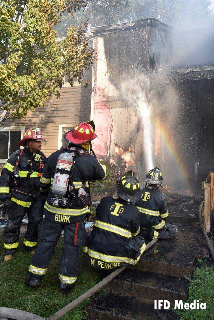 Firefighters conduct a hosestream on the apartment's exterior