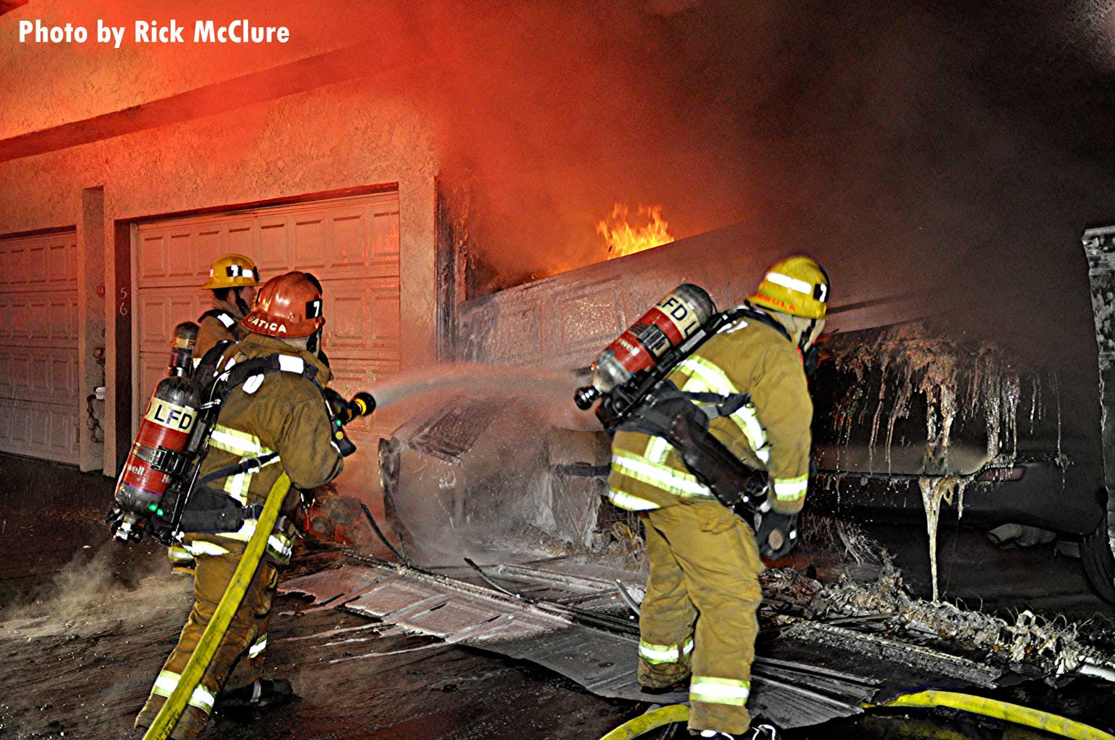 LAFD crews with a hoseline gain access to garage