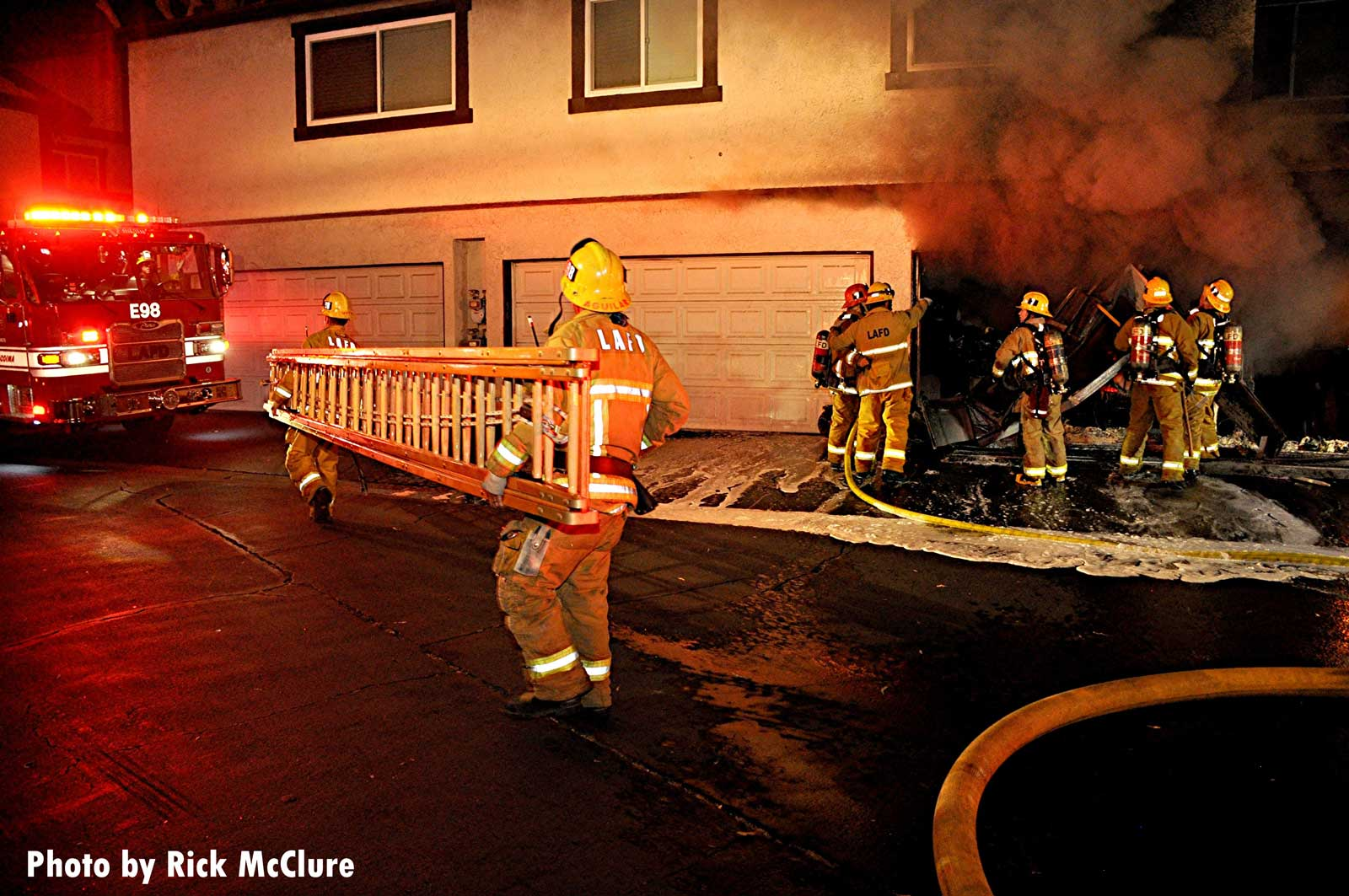 Firefighters bring a ground ladder as other members in the background use hoseline in garage