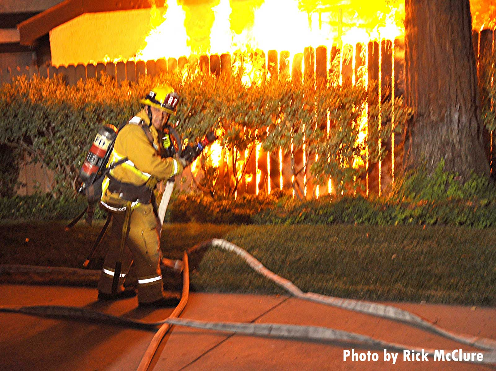 Firefighter with a hoseline near a fence as fire rages in a building in the background