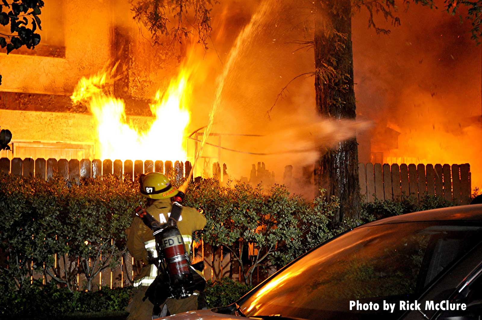 Firefighter with a hose as flames burn in the background