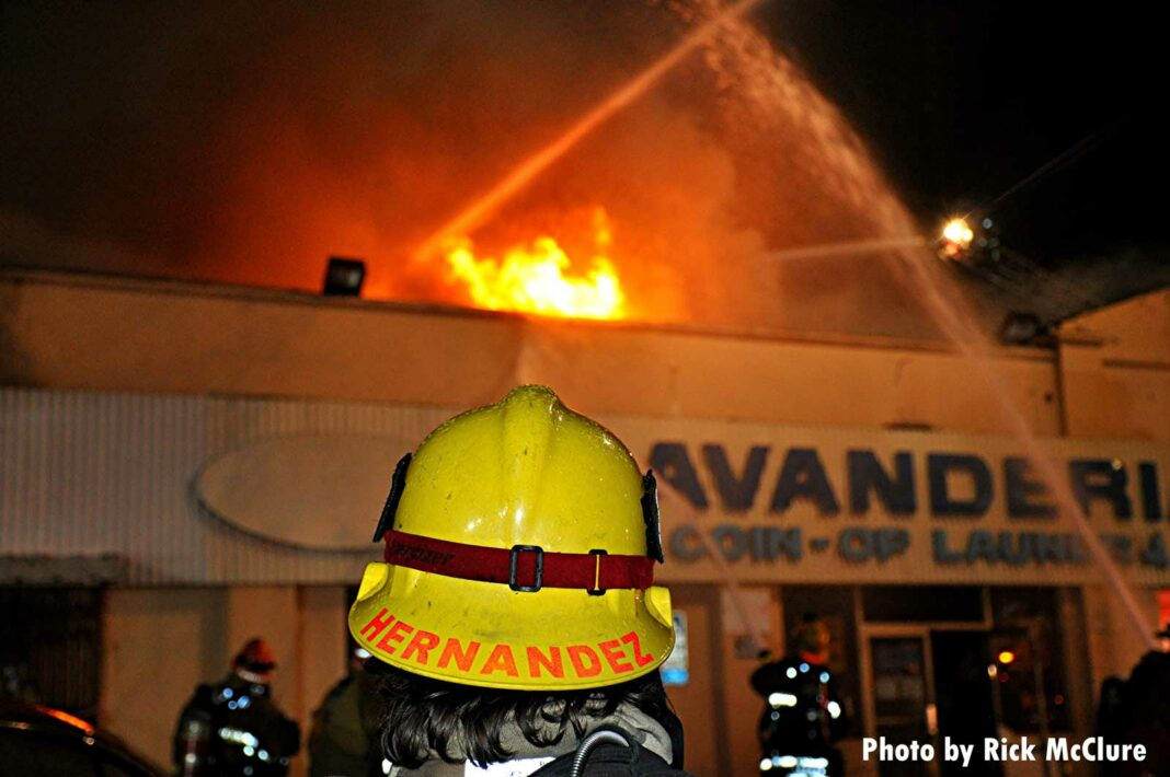 LAFD firefighter with helmet and fire raging in the building behind
