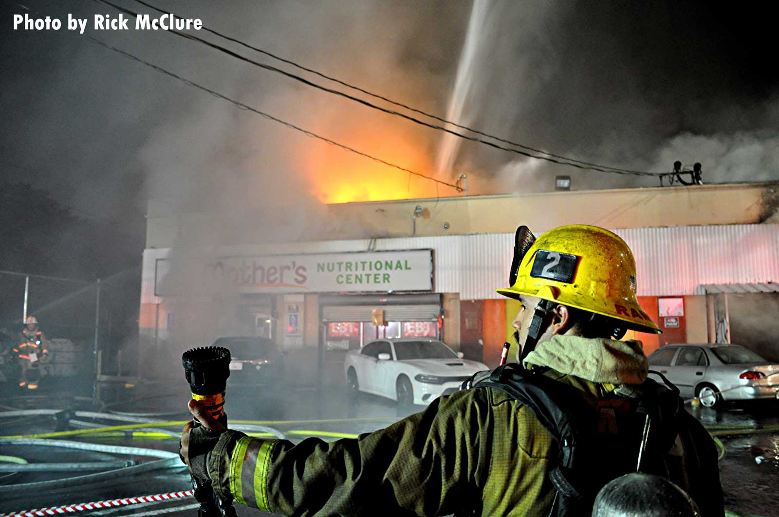 An LAFD firefighter with a TIC as flames shoot from a building in the background