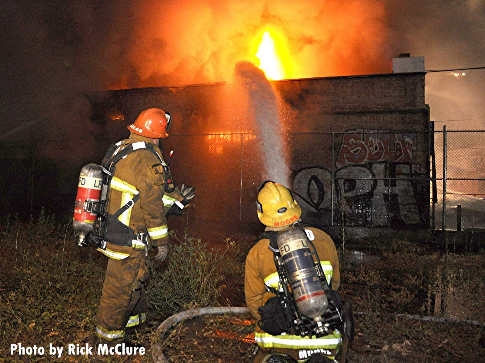 Firefighters with a hoseline putting water on flames