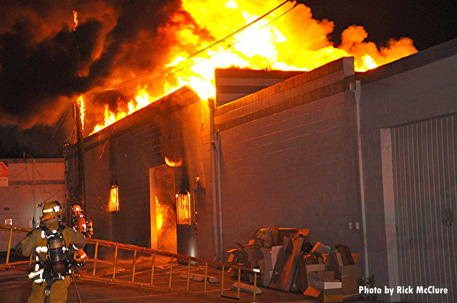 Shot of flames shooting through the roof of the building