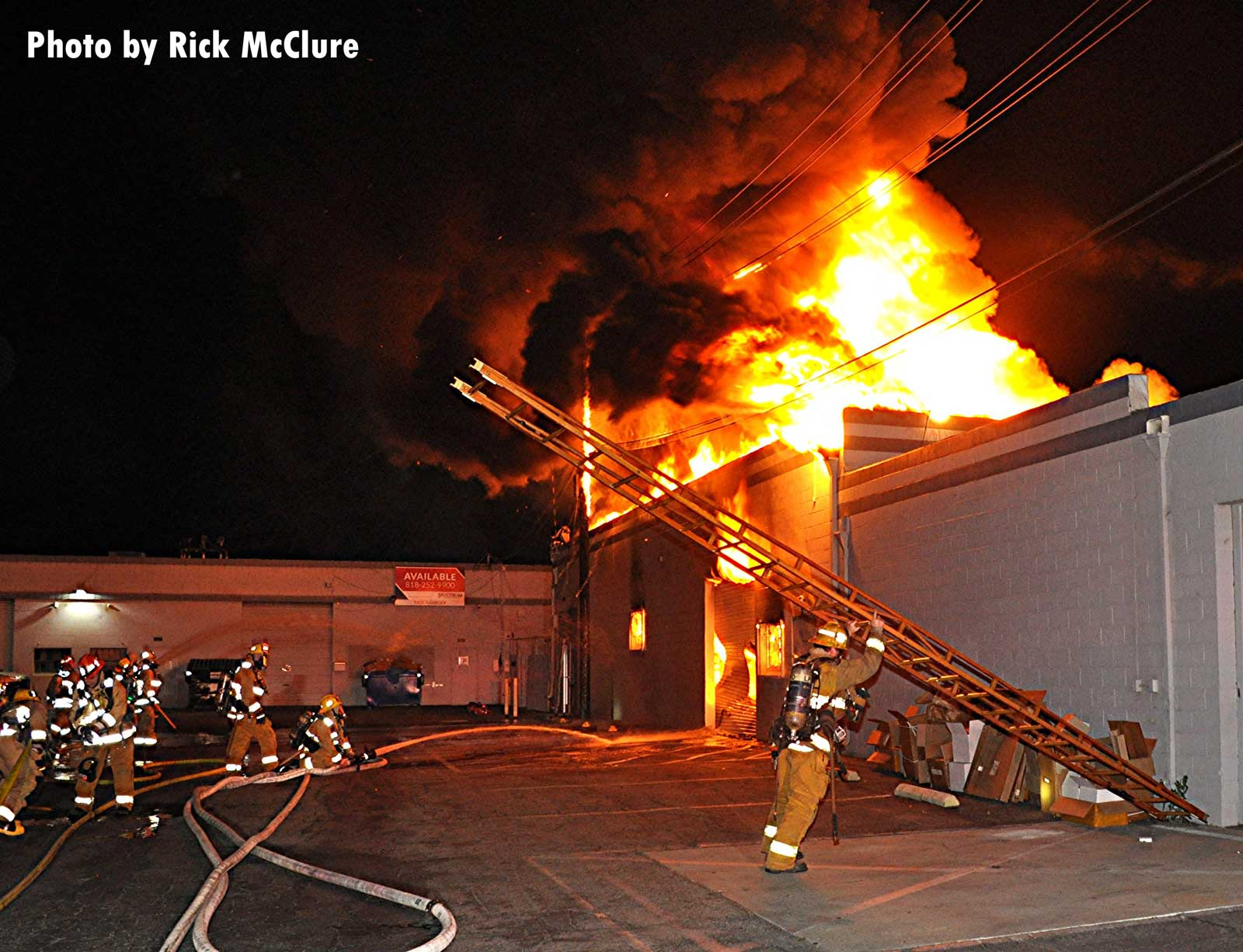 Flames rage outside a building as LAFD crew members work