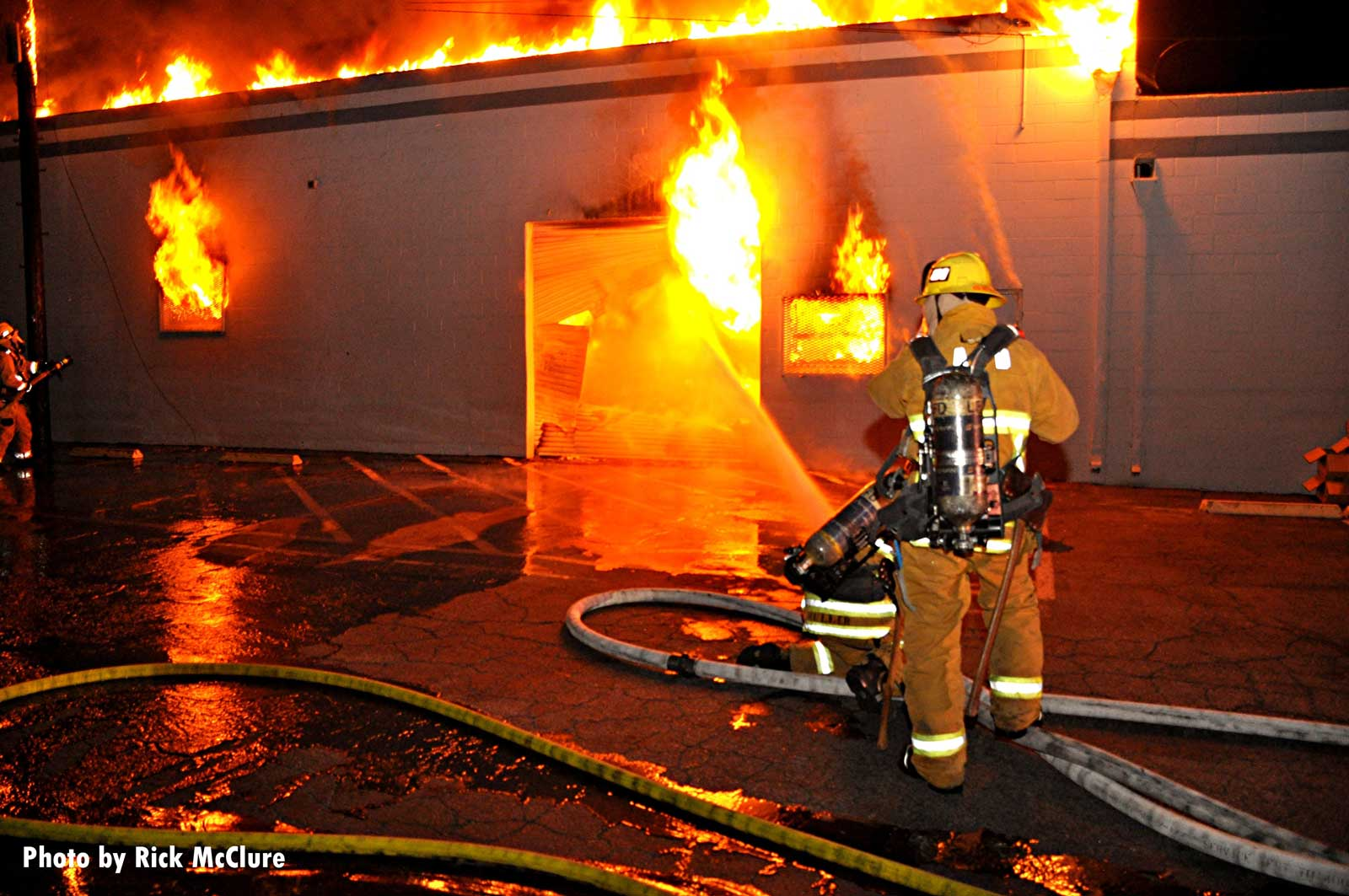 City of Los Angeles firefighter with flames shooting through a building in the background