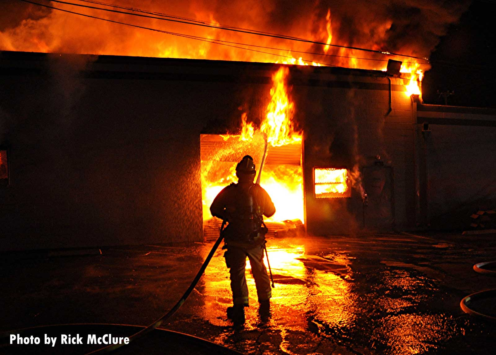 Firefighter silhouetted by flames in the burning building