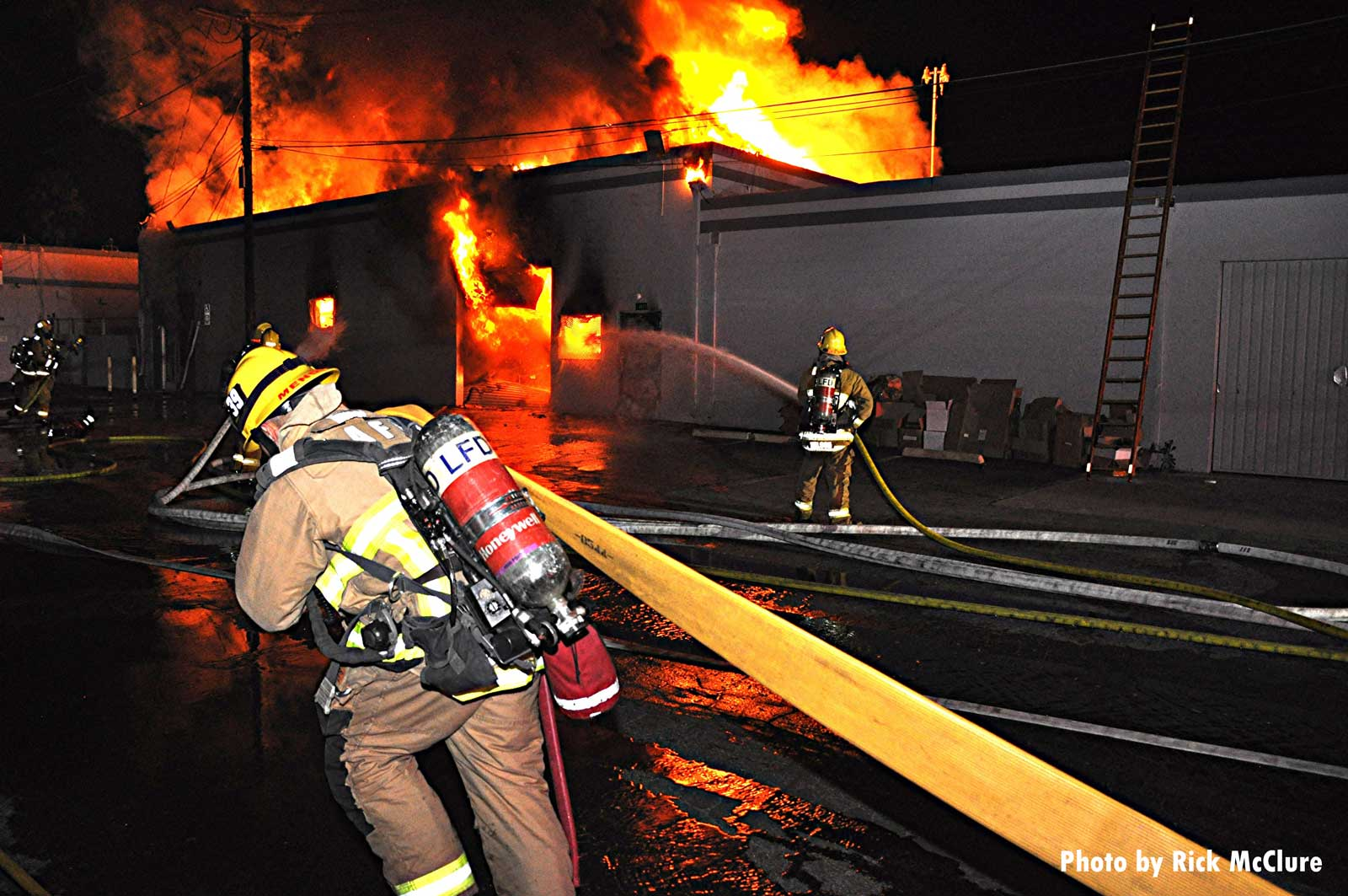 LAFD firefighter pulls a hoseline at the scene of the fire