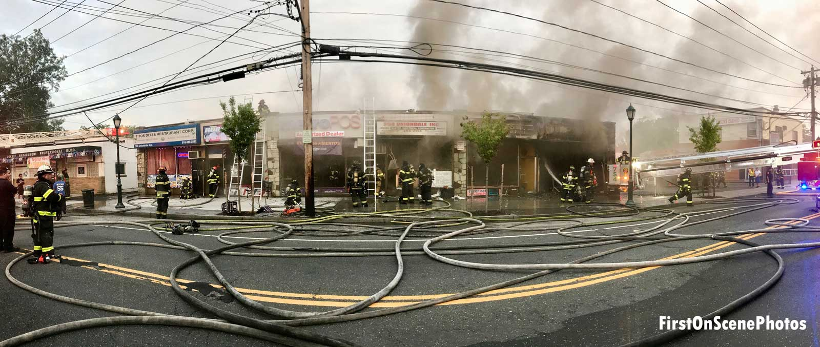 Panorama view of hoselines and multiple businesses burned in fire