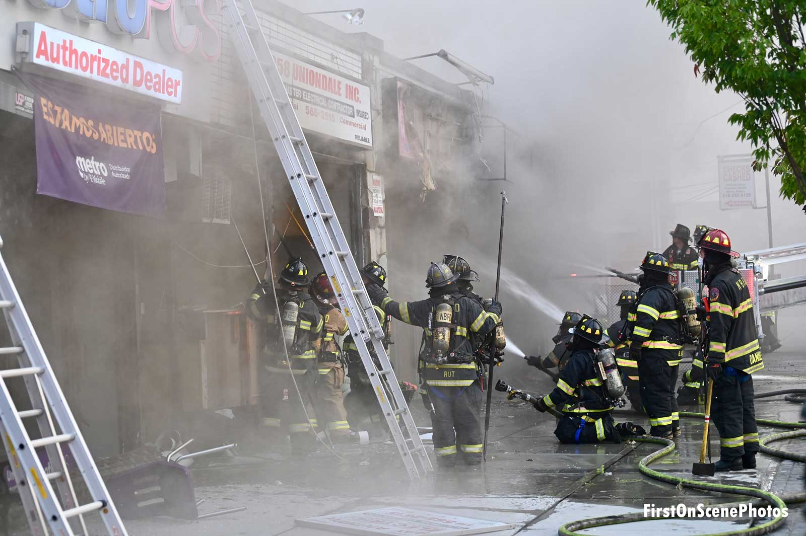Firefighters with a ladder outside a smoky business