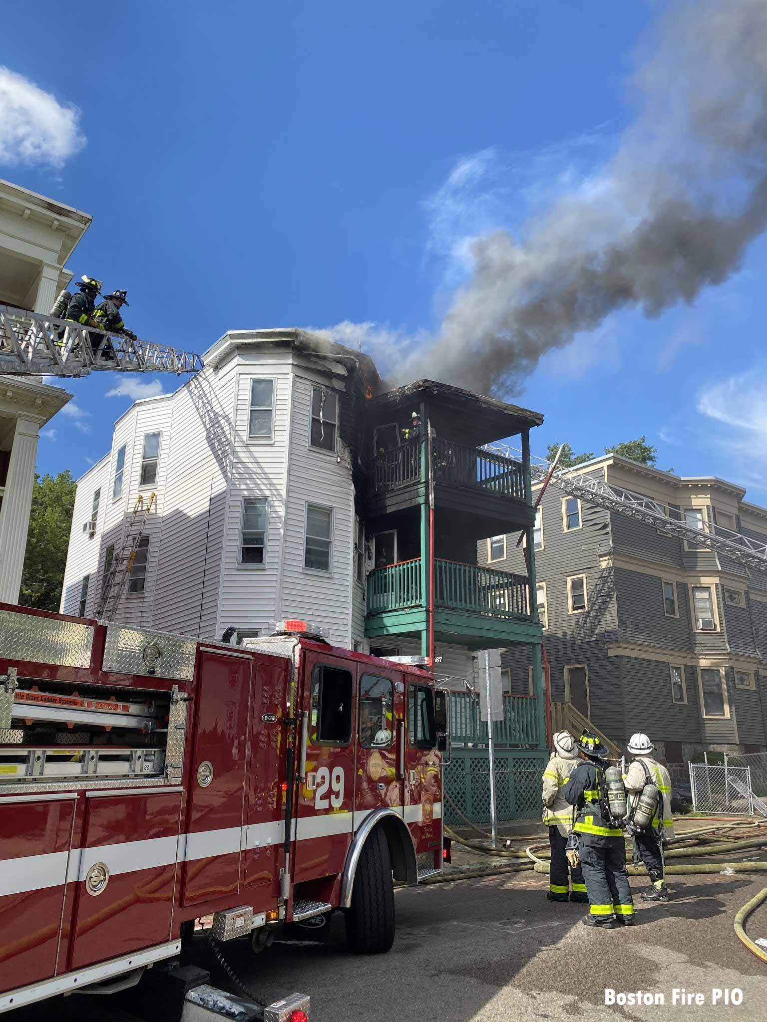 Smoke shows from the roof of the building with Boston fire apparatus and command staff in the front