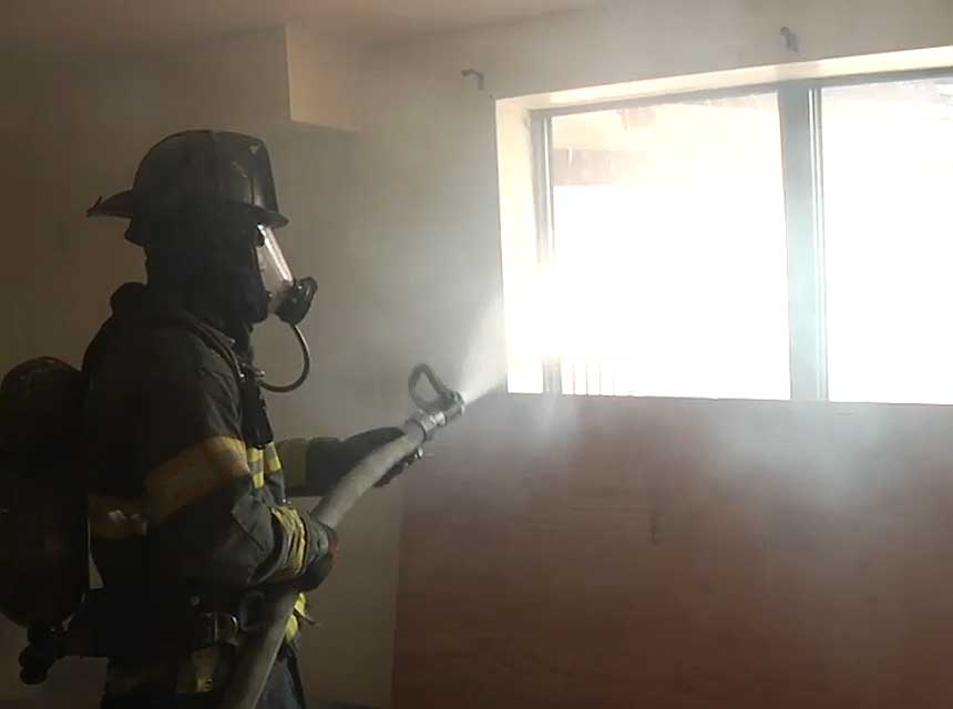 Firefighter with smooth bore nozzle performing hydraulic ventilation