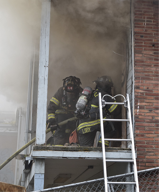 Crews create an entry point and are met with smoke under light/moderate pressure at the top of the door.