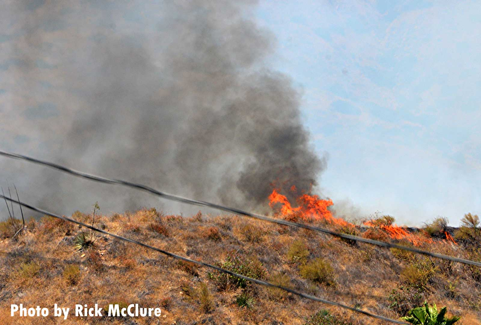 Flames crest a hill during a wildfire