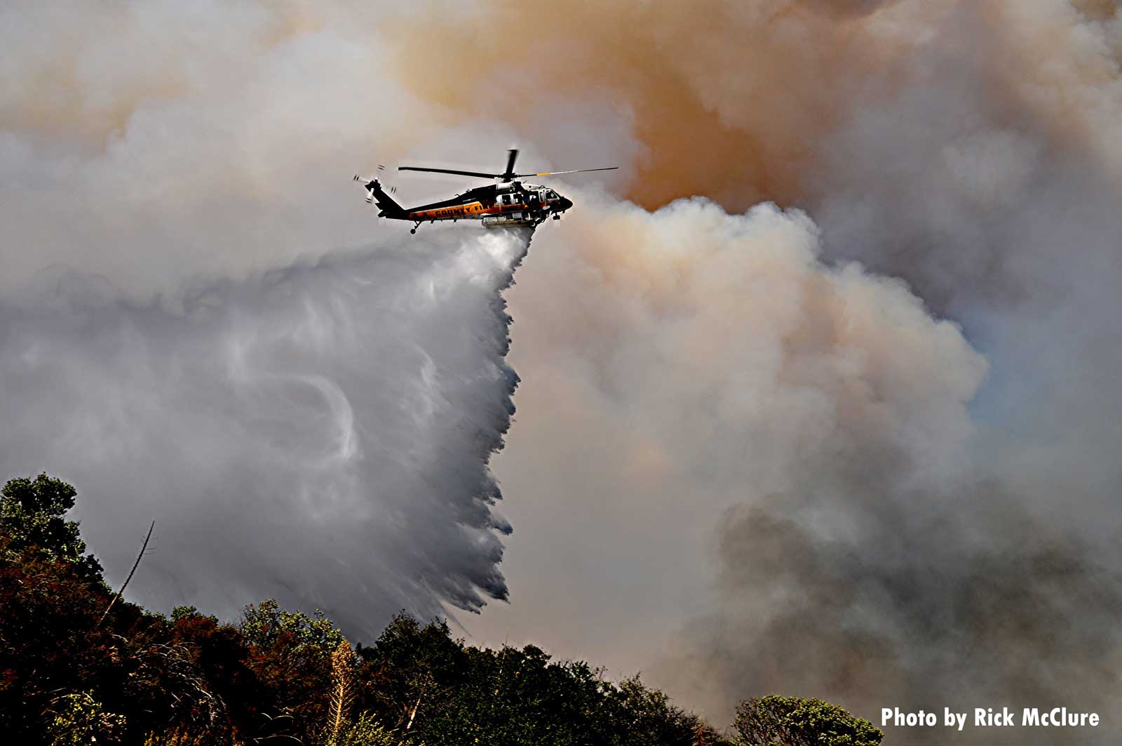 Helicopter drops fire retardant