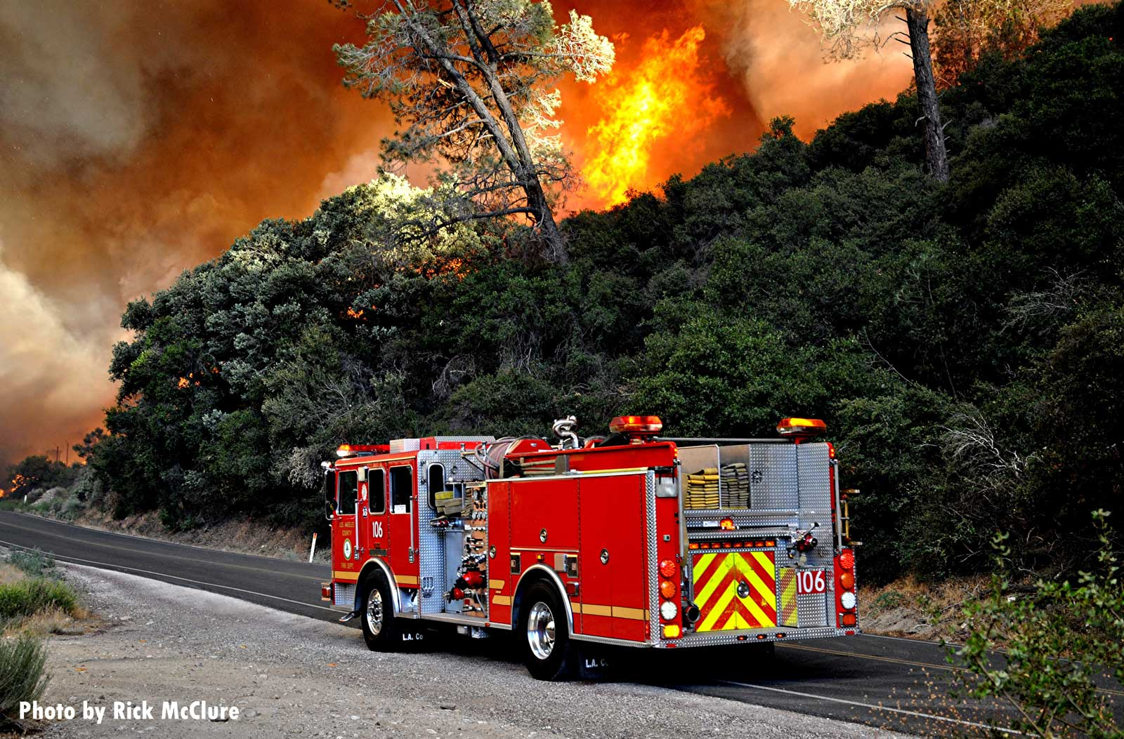 Fire truck with wildfire raging in background
