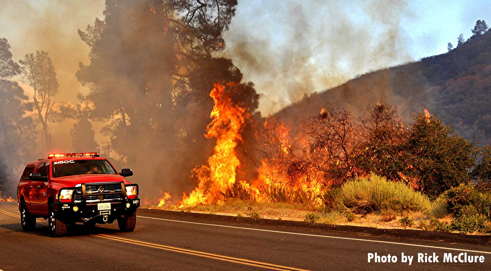 Fire vehicle near road with wildfire burning