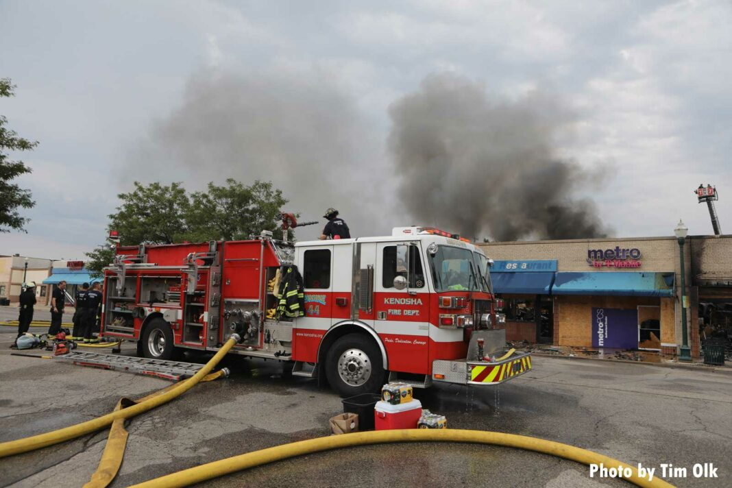 Fire apparatus with supply lines and smoke rising in the background