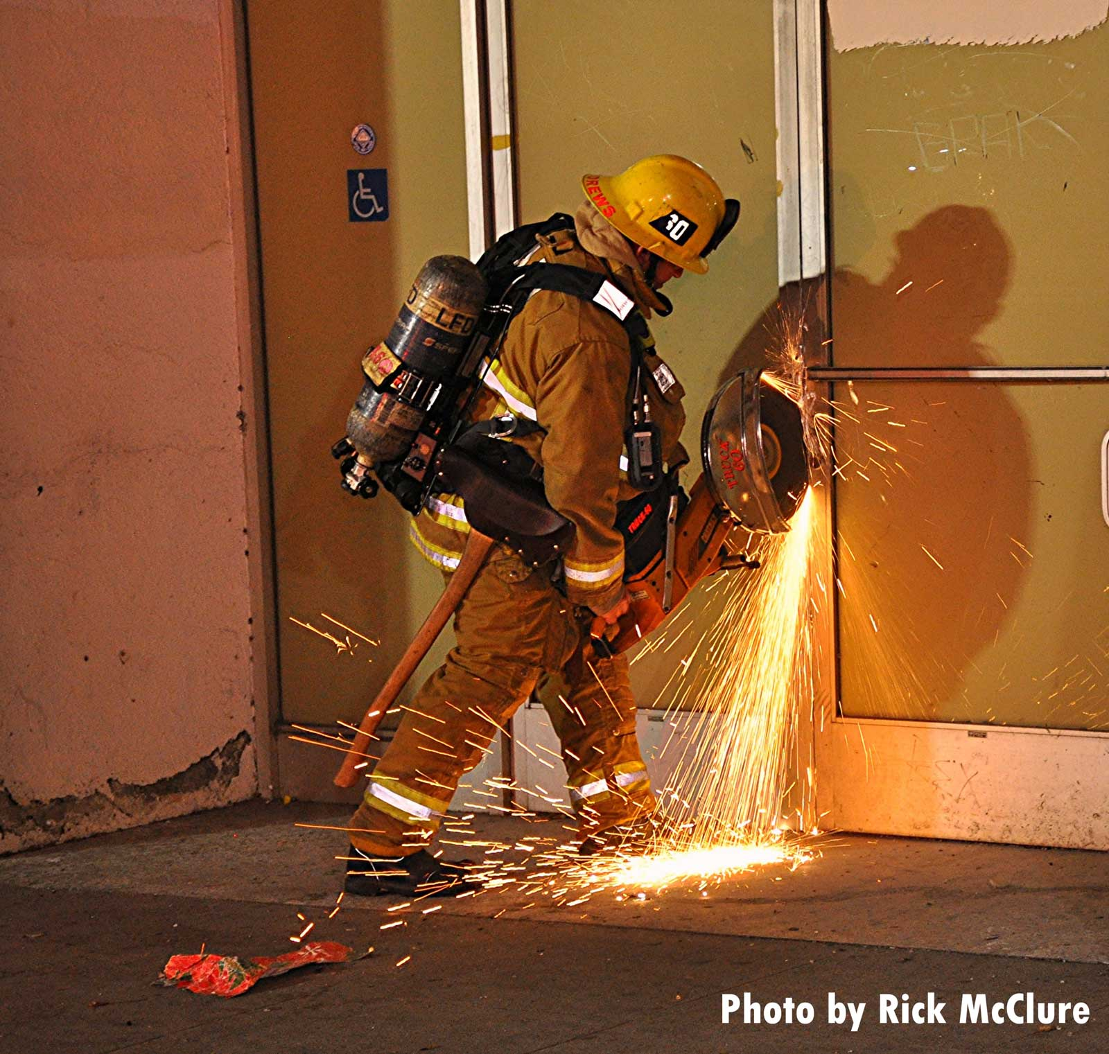 Firefighter cutting through a door