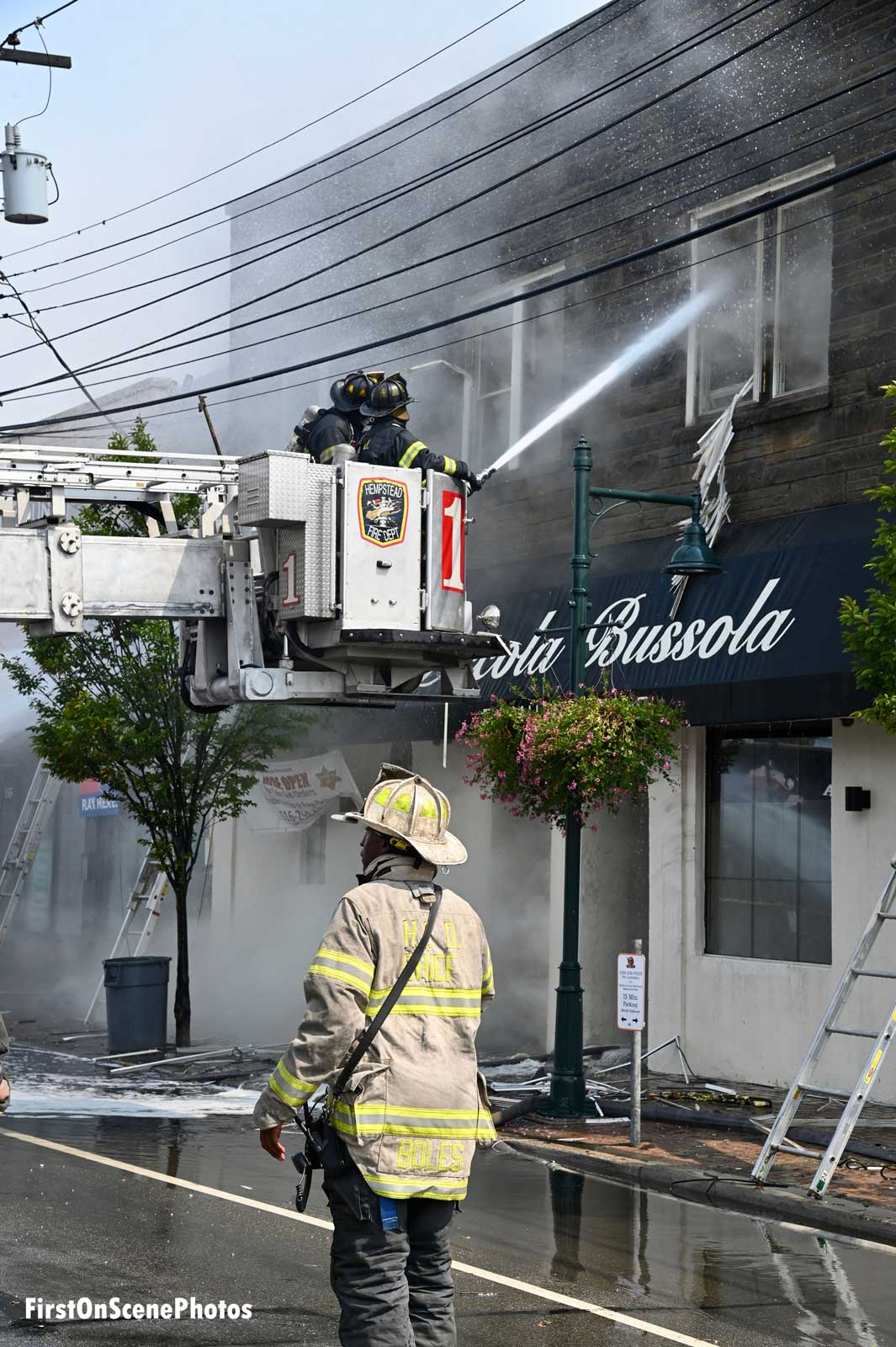 Firefighter in tower ladder aims stream into the building