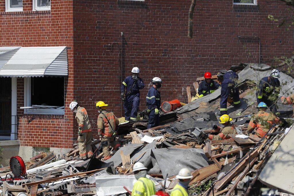 Authorities walk among the piles of debris