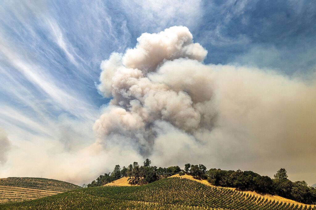 Fire smoke rises in background with fields in the foreground