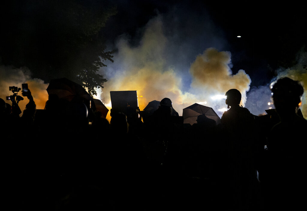 Smoke rises past Portland cops and crowd