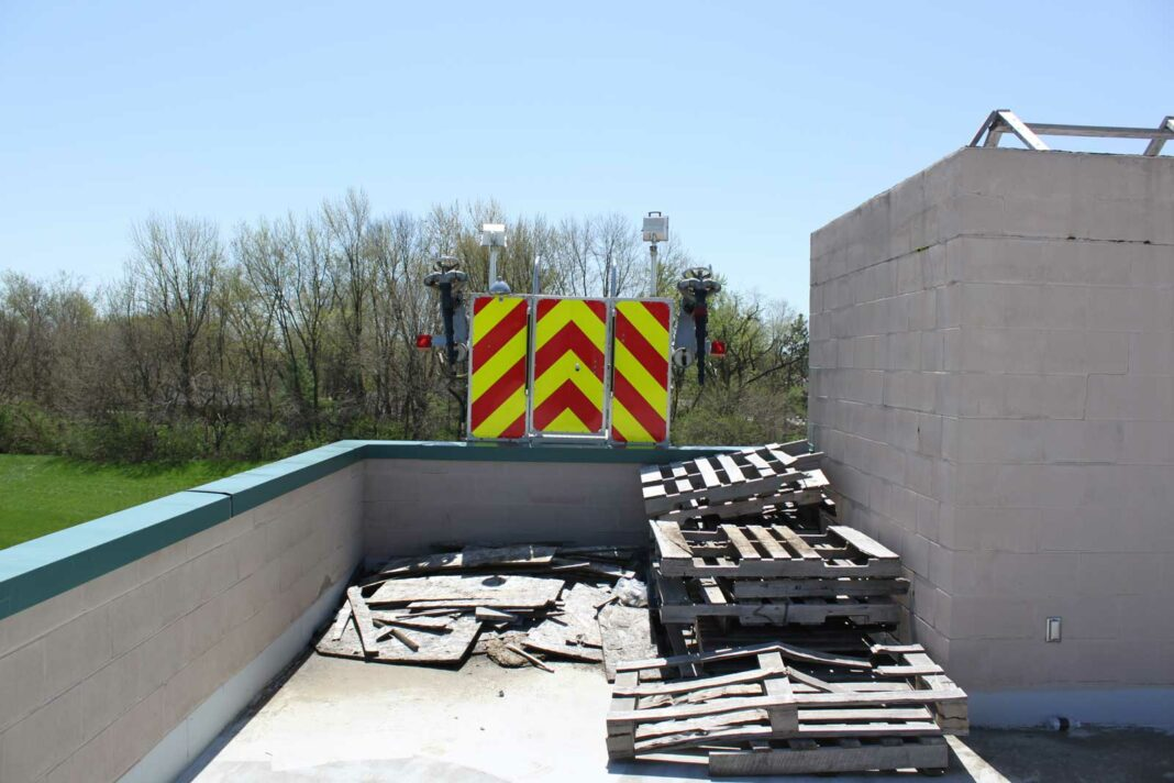 Tower ladder over flat roof with various debris