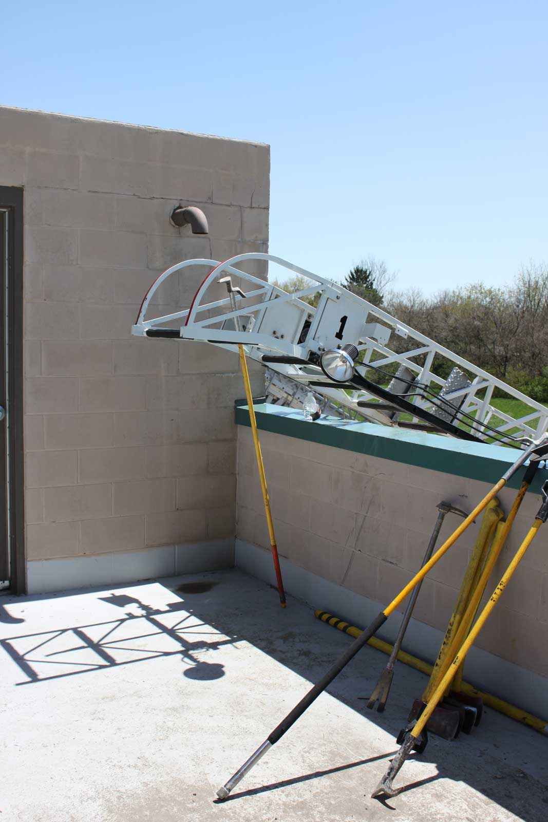 Aerial tip extending over parapet wall onto flat roof with firefighter tools