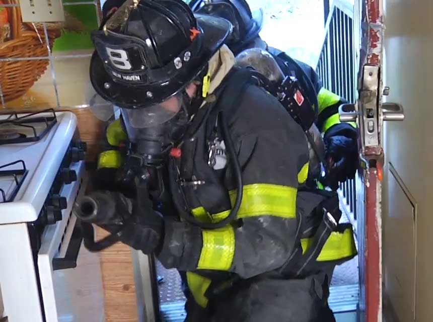 Firefighters using clamp for door control
