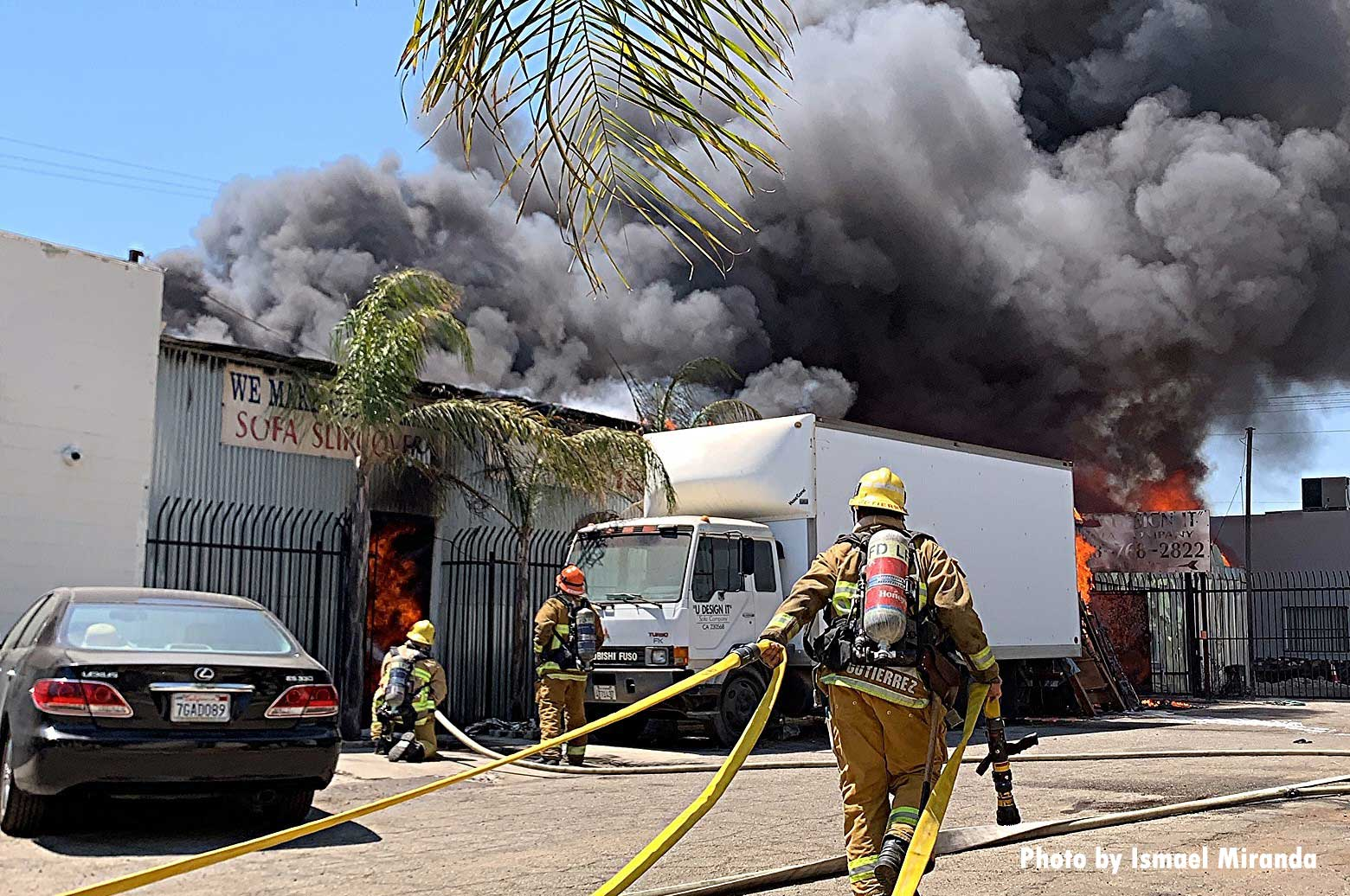 LAFD firefighters drag hoselines towards building with smoke showing