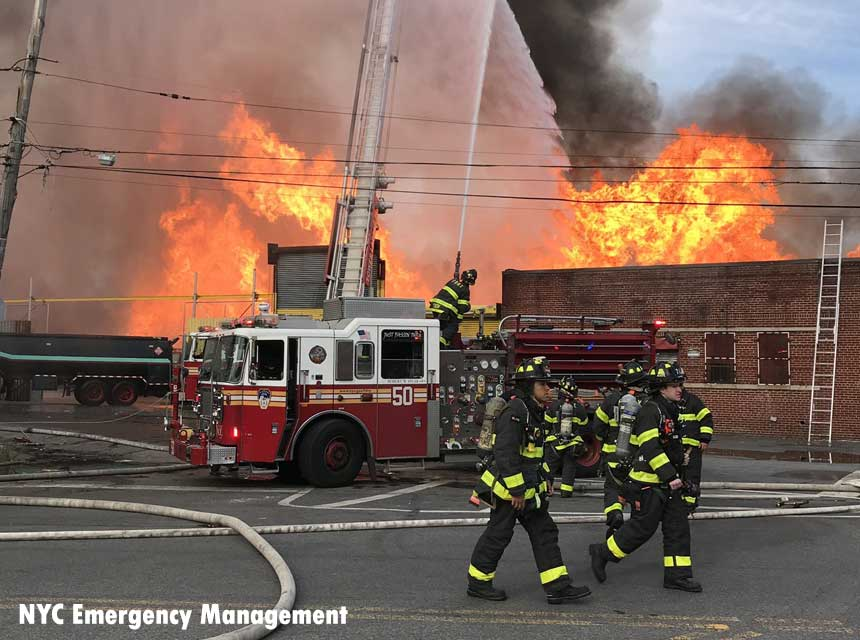 Members of the FDNY and rigs at Bronx junk yard fire