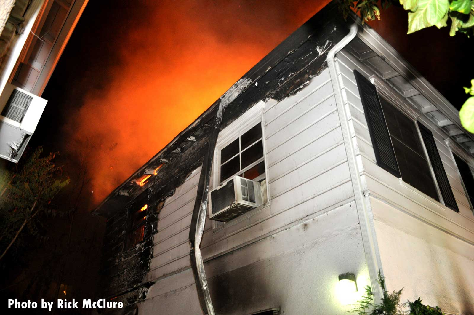 Looking up at flames atop the home