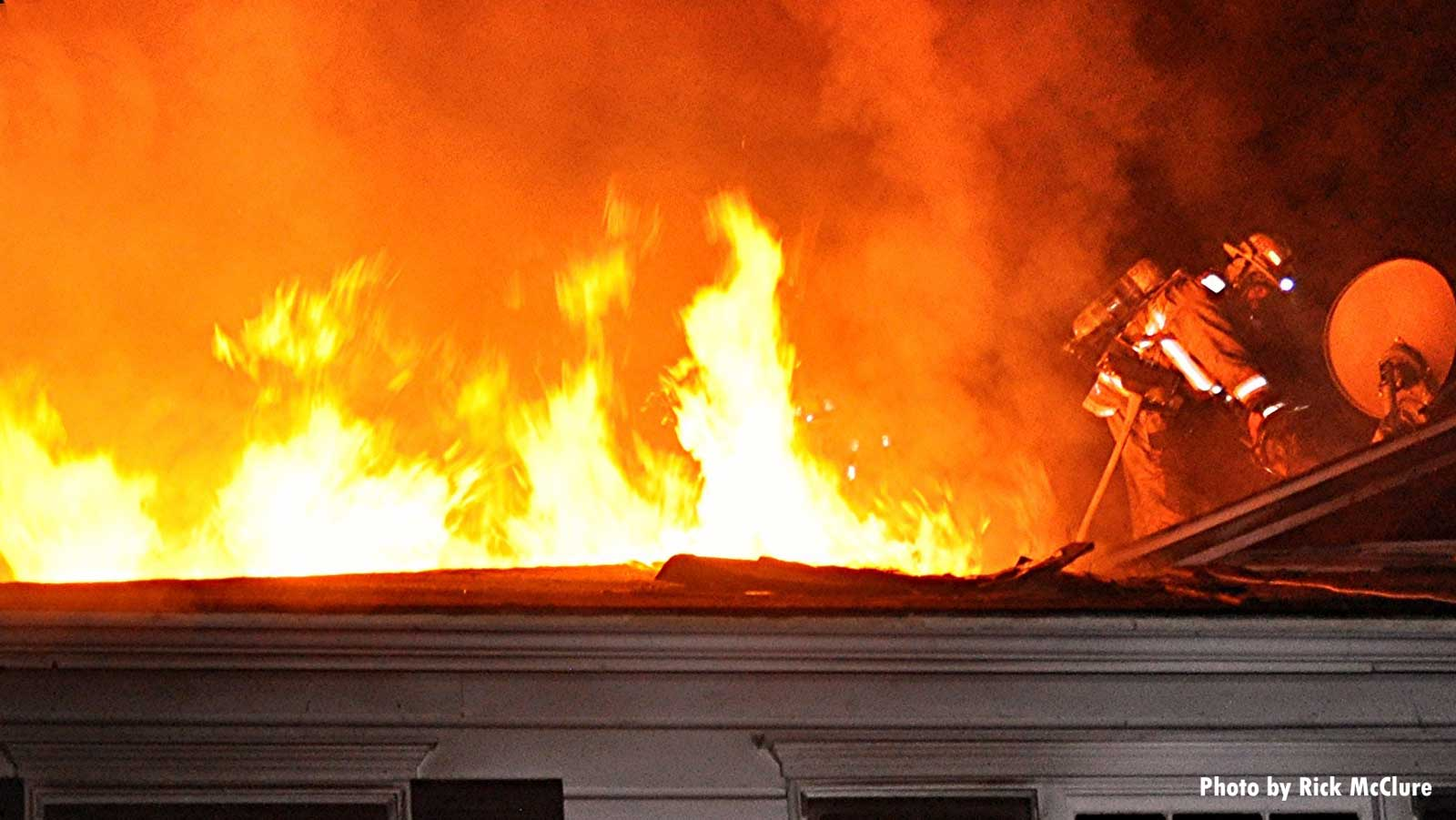 A firefighter on the roof with flames shooting through it