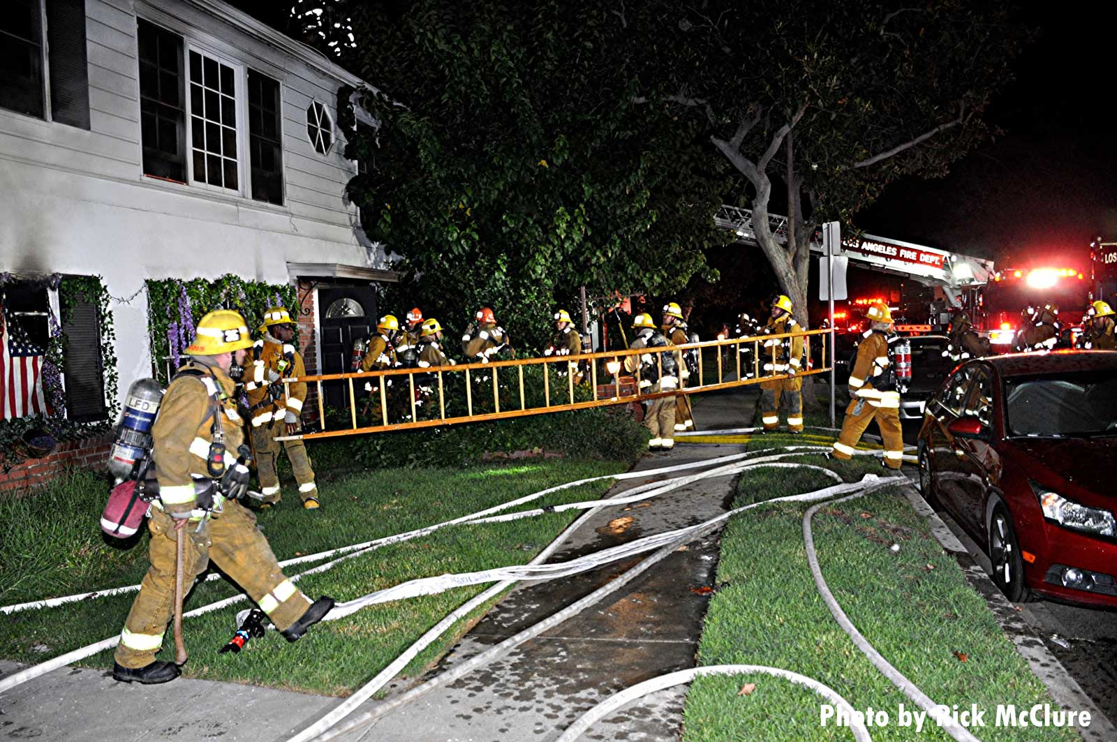 Firefighters with a ladder at Los Angeles house fire