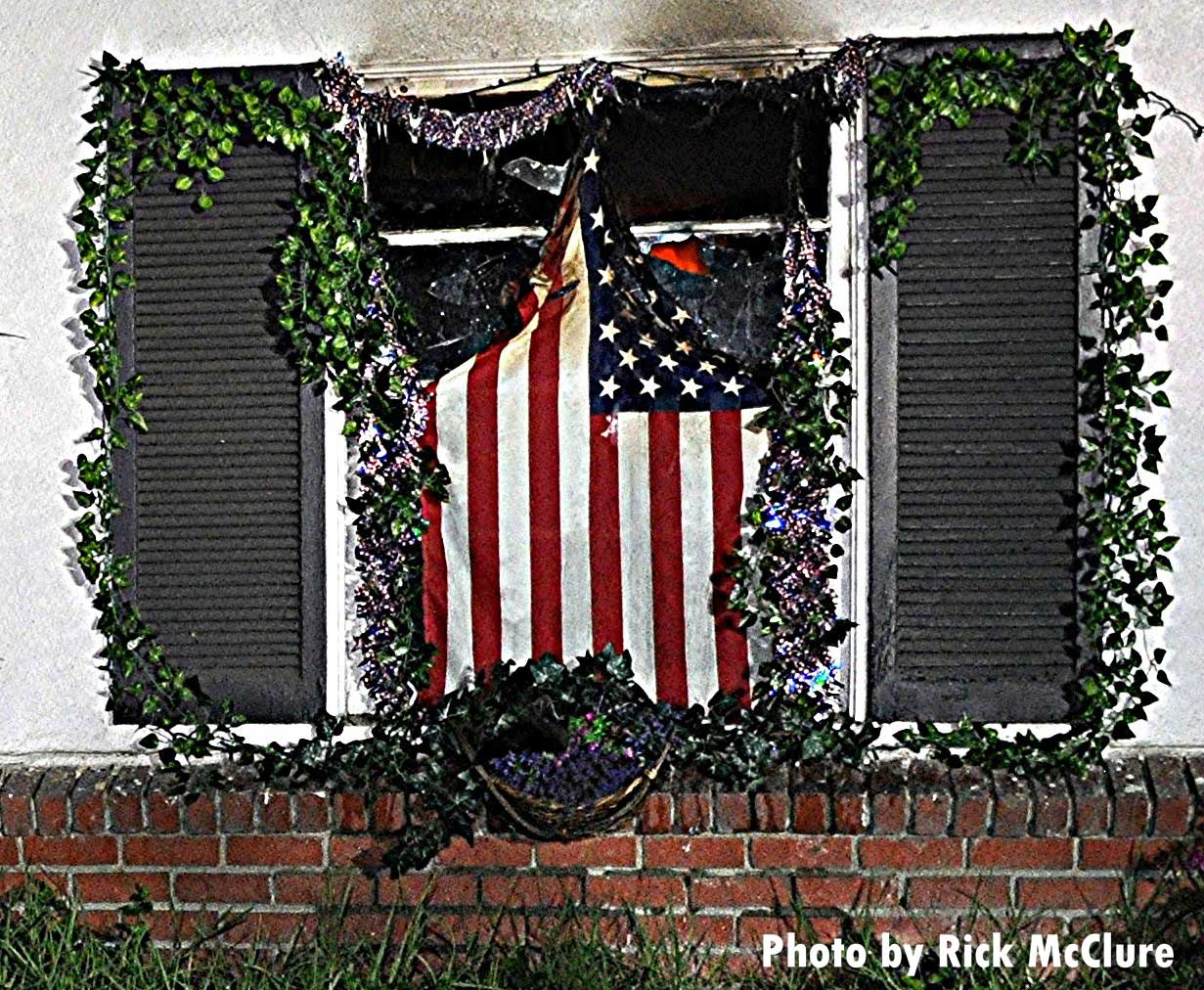 Photo of American flag hanging in window at house fire