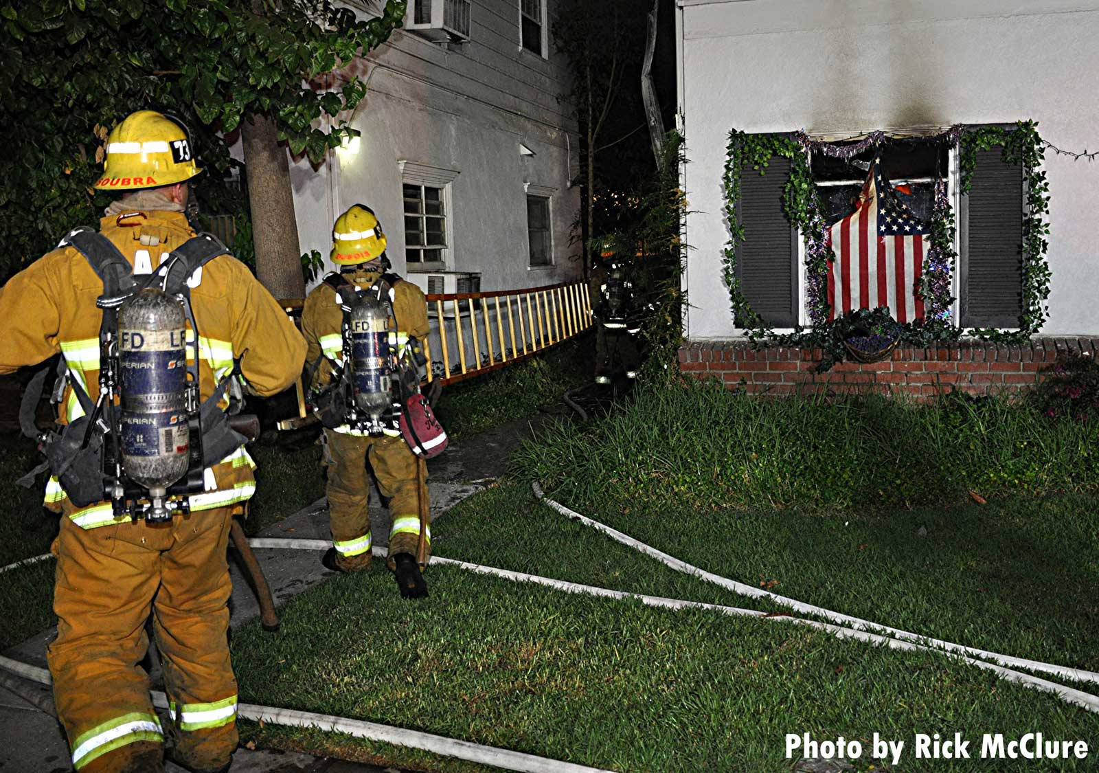 LAFD firefighters advance a ladder between structures while U.S. flag hangs in window