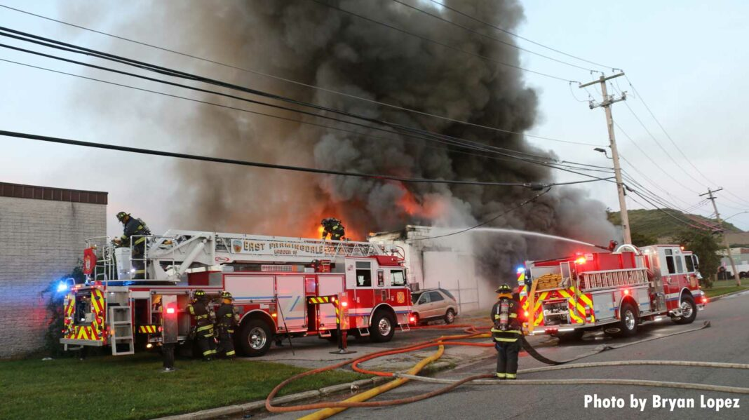 Fire apparatus with smoke rising from commercial structure