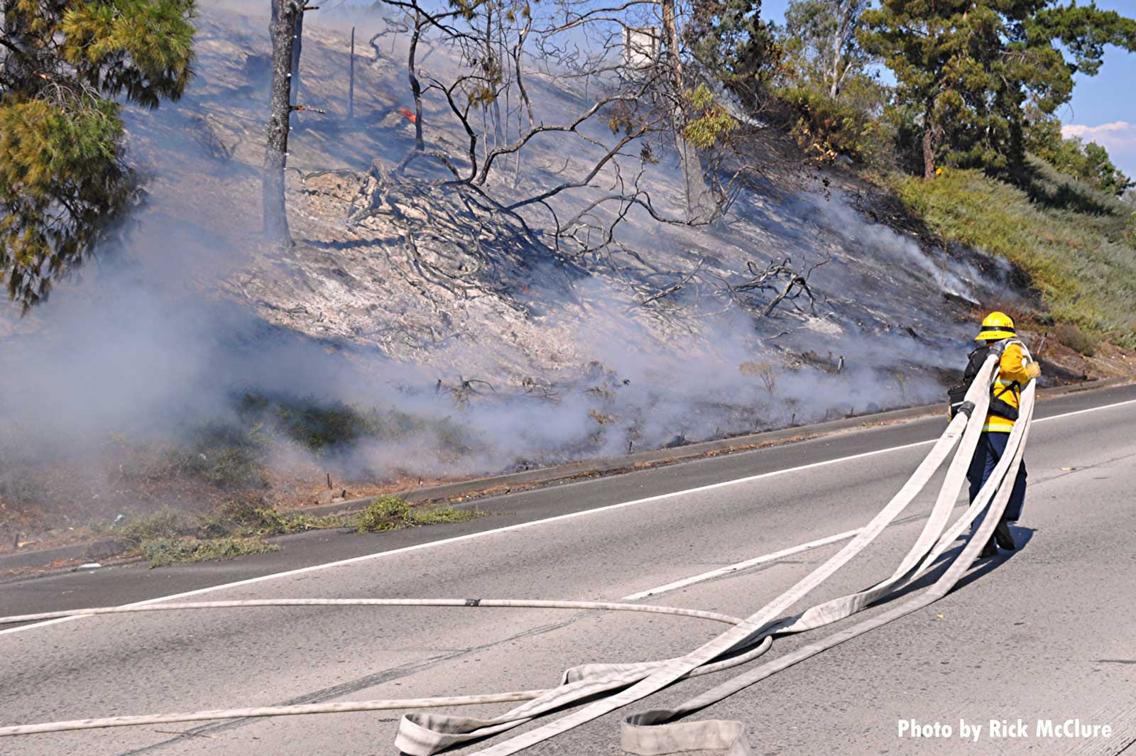 Firefighter stretches out hoseline at brush fire