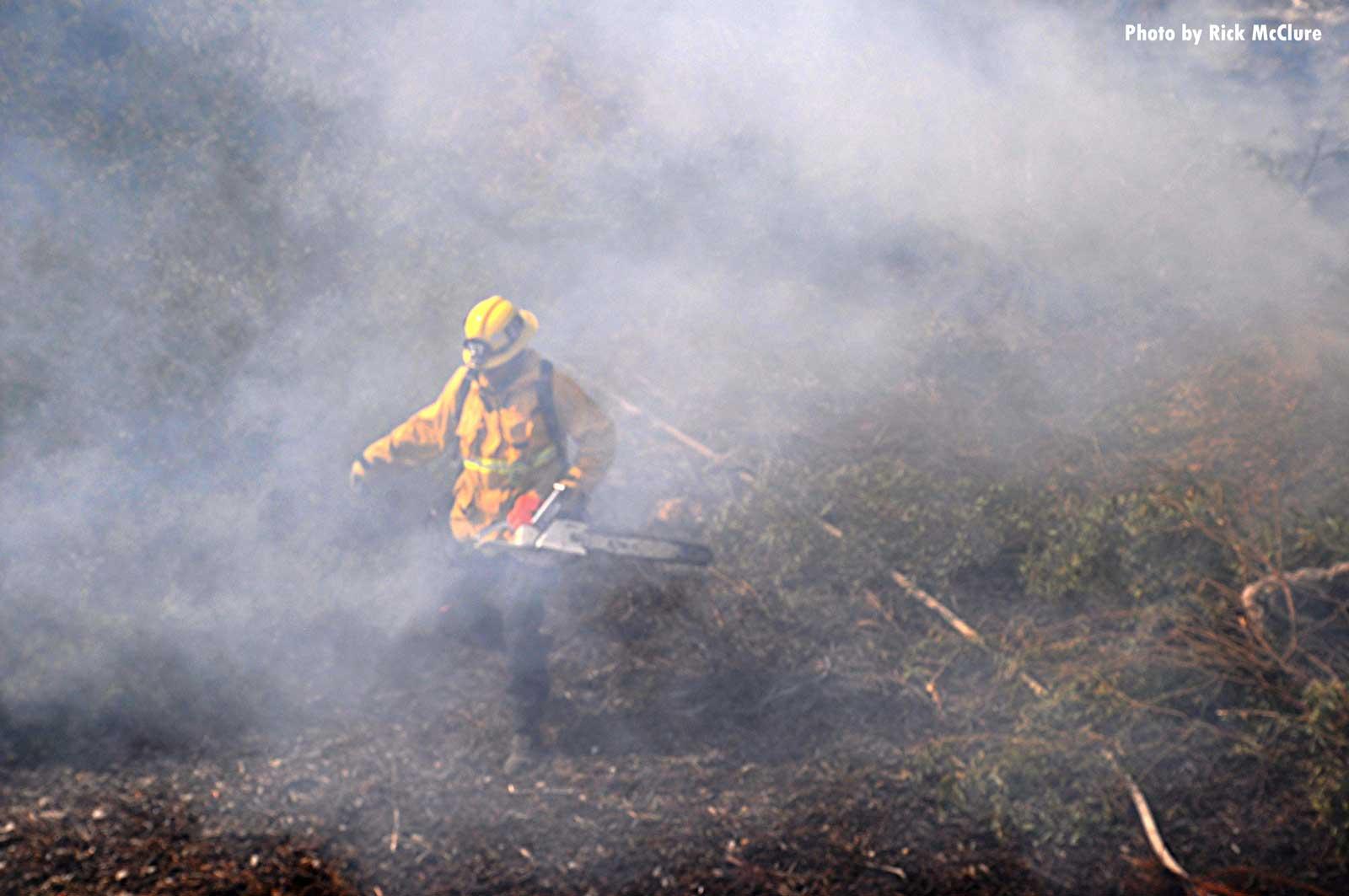 Firefighter operating in brush fire smoke