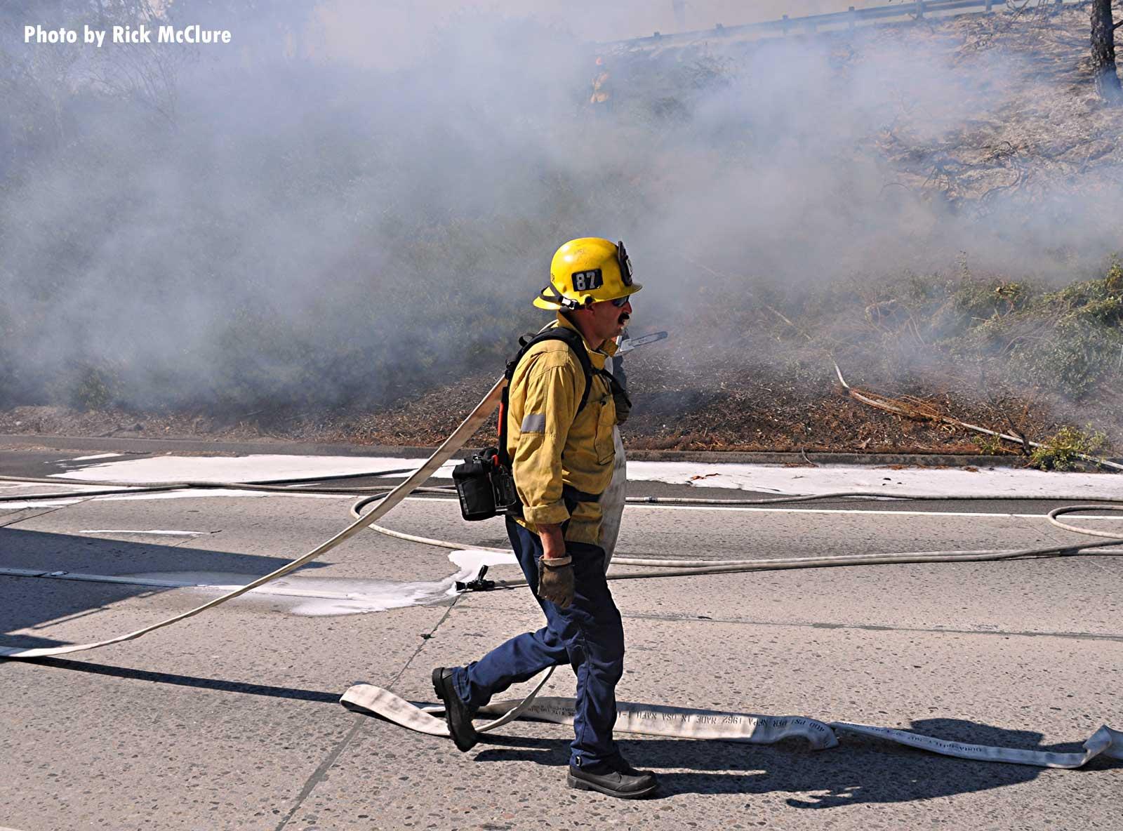 Firefighter walking along the roadway in brush fire smoke