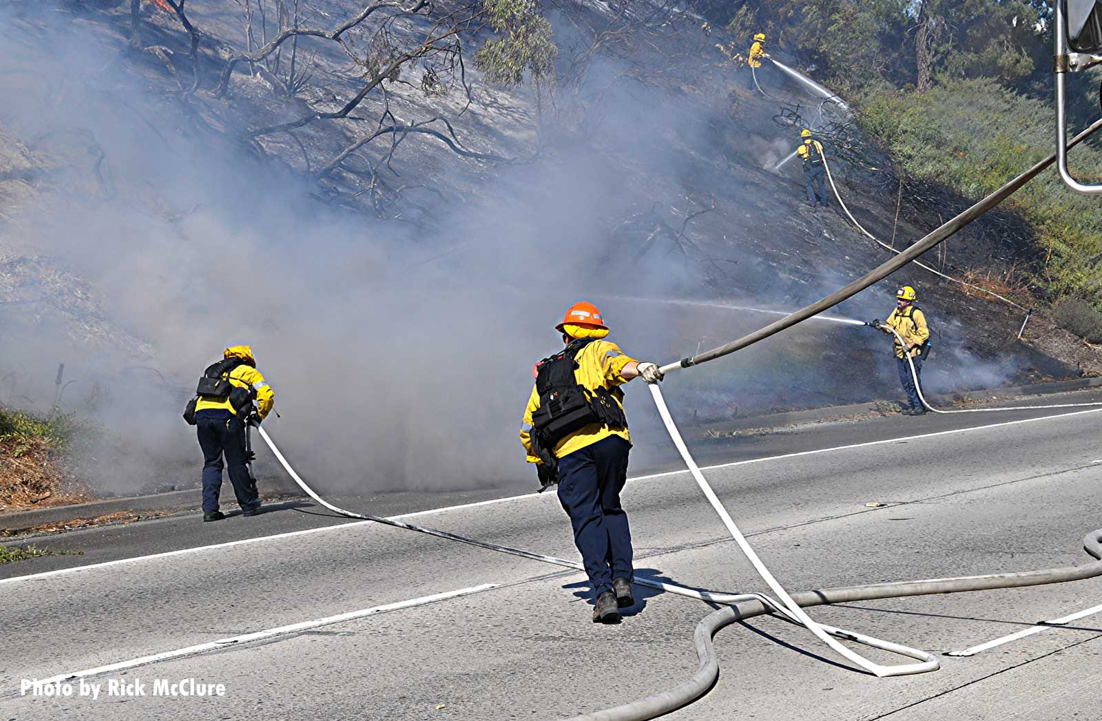 Firefighters move hoselines at California brush fire
