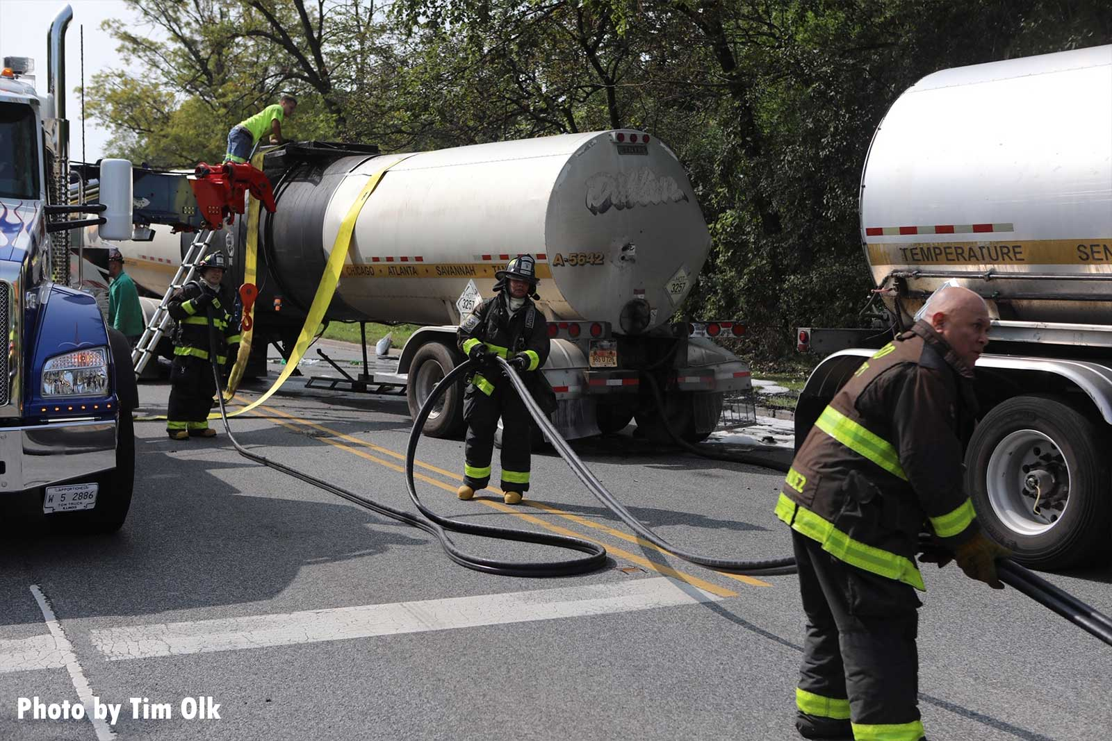 Firefighters with hoselines at the scene of the tanker incident