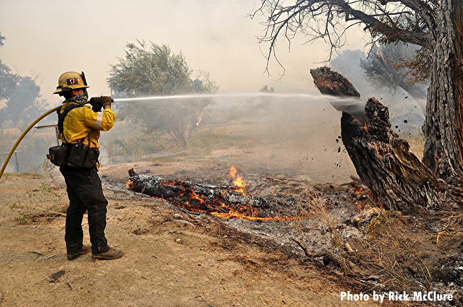A firefighter applies water on the flames