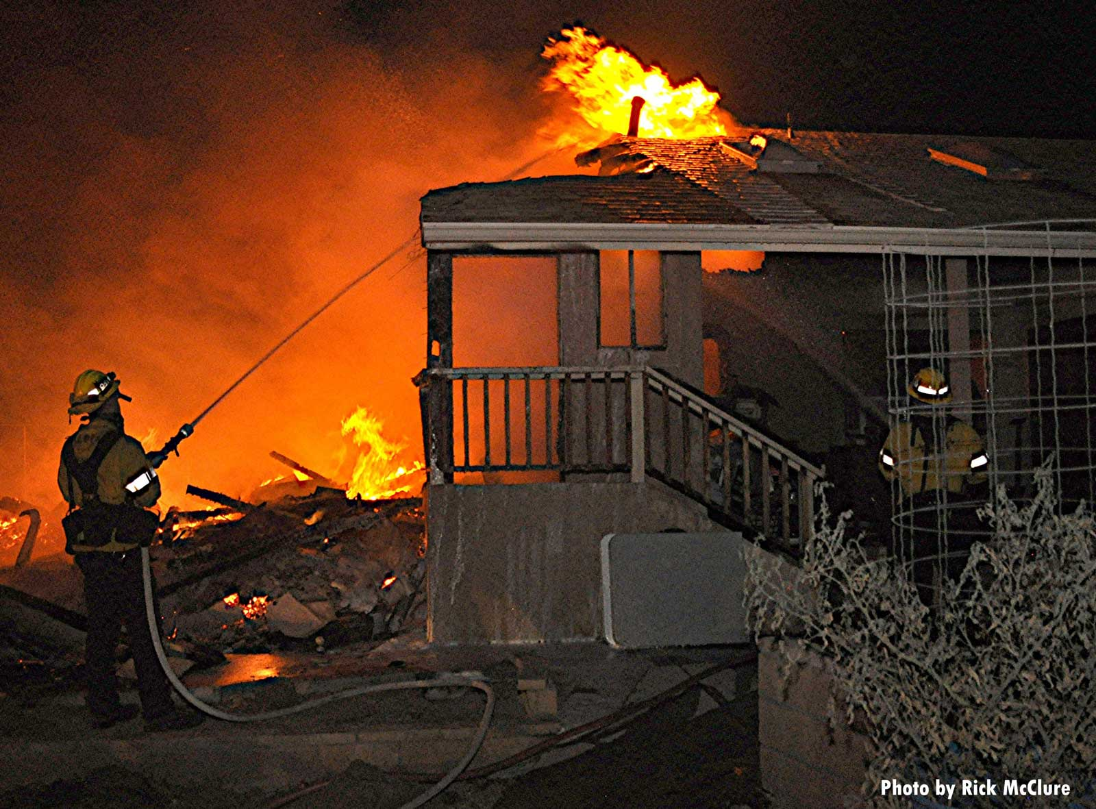Flames consume a building as firefighter applies water