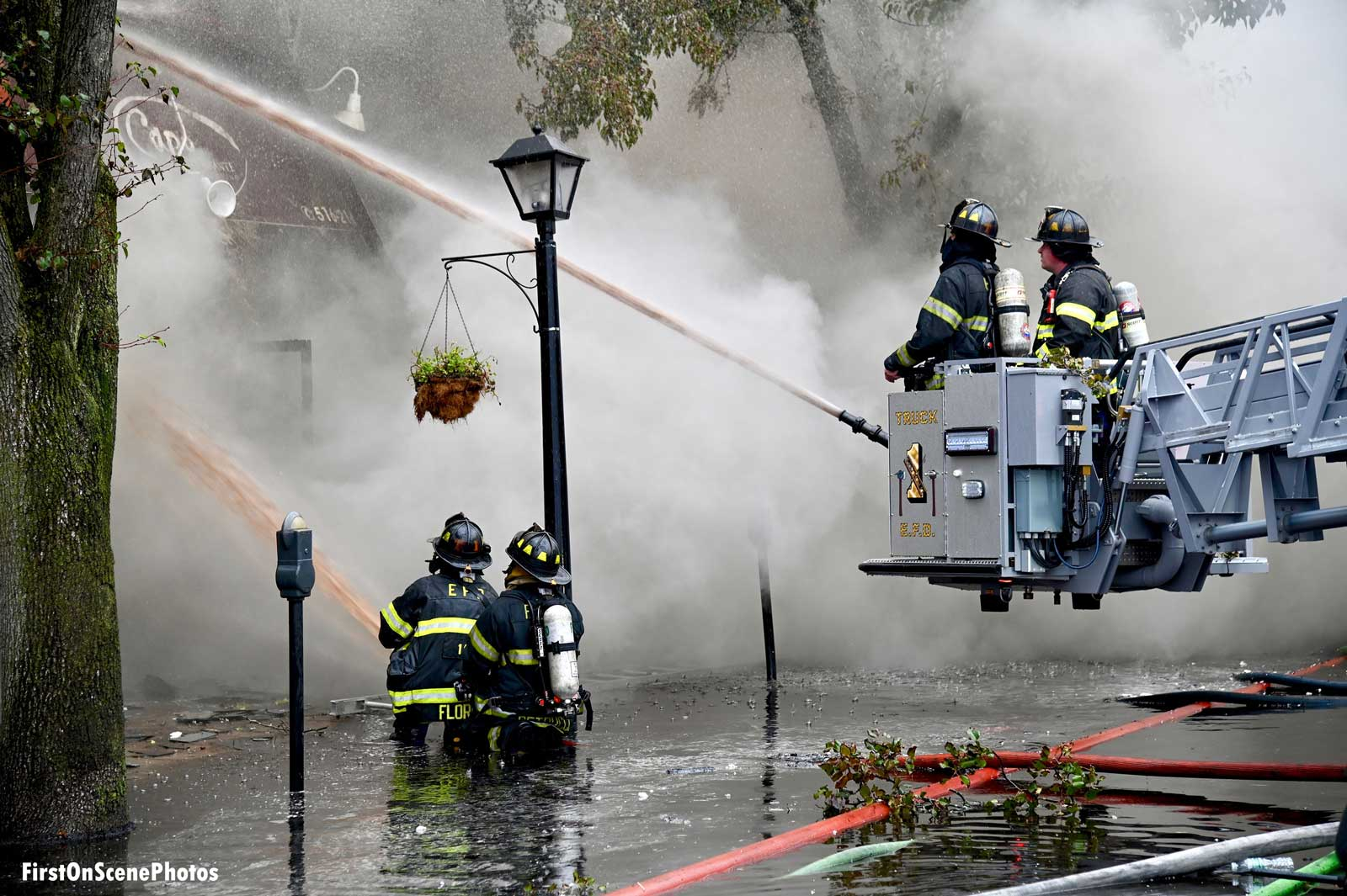 Firefighters on the ground and in a bucket aiming hose streams